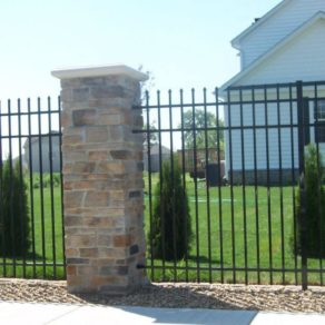 Iron fence with stone columns, if looking for affordable fence builders Munster.