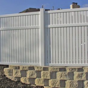 A home's newly installed vinyl fence sitting on bricks, if looking for affordable fence installers Tinley Park.