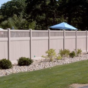 Tan vinyl fencing with rock landscaping, if looking for affordable fence builders Valparaiso.